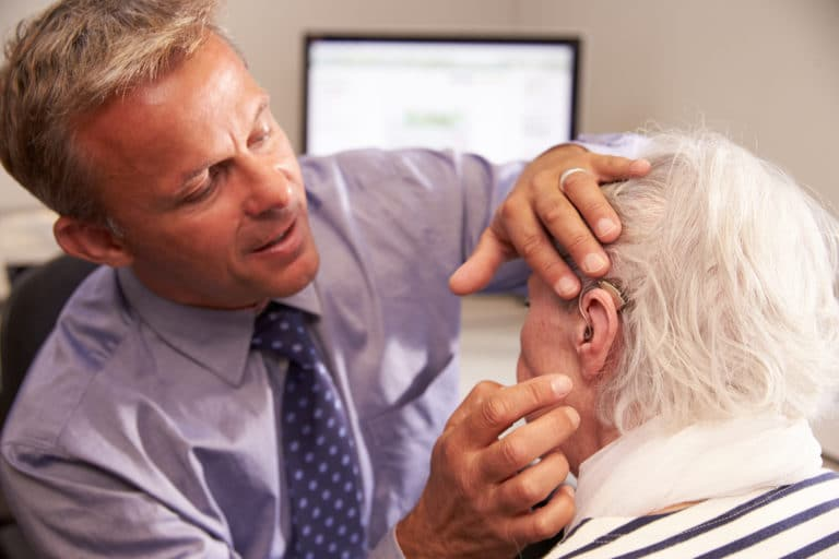 Audiologist fitting a man with hearing aids