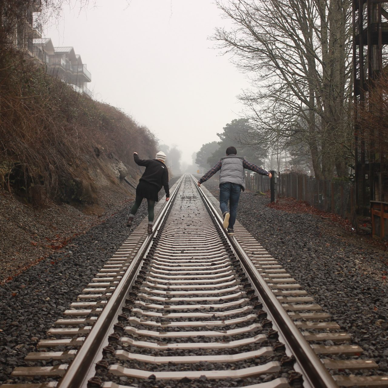 two people balancing on railroad tracks