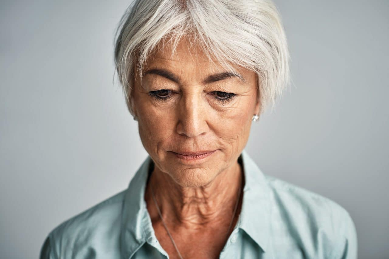 Studio shot of a senior woman posing against a grey background