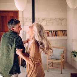 Playful mature husband and wife having fun, celebrating, dancing and laughing together in living room